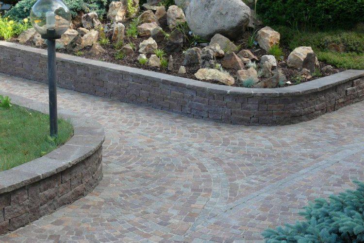 Immagine di un giardino esterno, arredato con pietra Porfido per pavimentazioni e rivestimento muri, e copertine con coste tranciate.