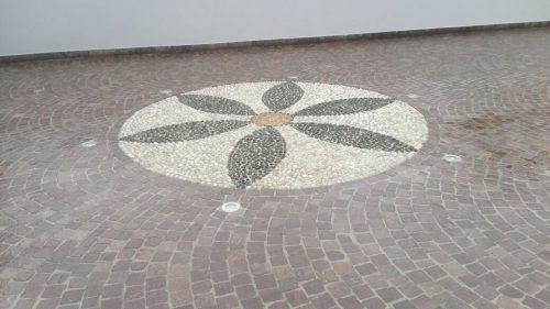 Decorazione di pavimento con fiore a sei petali in sassi da fiume